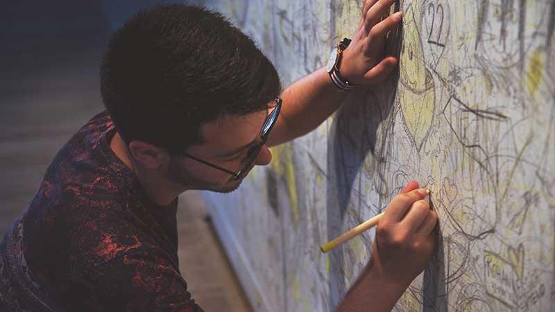 בחור מצייר על קיר